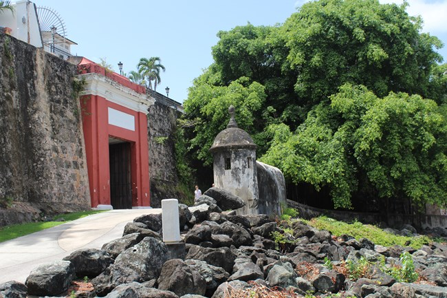 The San Juan Gate with sentry box on the right and the El Paseo Trail in front