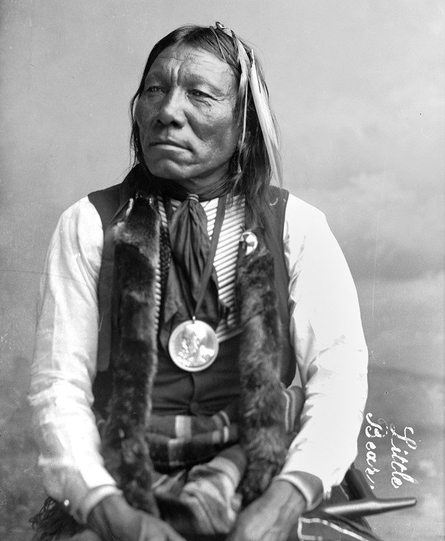 Photographed here in 1891 in Washington, D.C., Little Bear barely survived the Sand Creek Massacre. A federally-issued peace medal hangs from his neck.