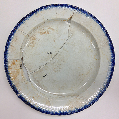 A re-assembled early 19th century pearlware plate with a dark blue rim.