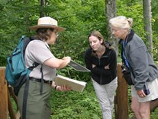 A ranger shows visitors historical images as they tour Rapidan Camp.
