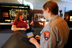 A uniformed park ranger use a Ubi Duo device to assist a visitor at the Visitor Center kiosk.