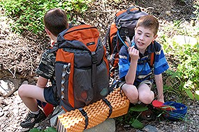 Two little boys wearing backpacks sit and rest