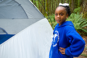 A little girl stands next to a tent
