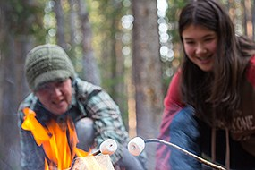 A woman and a youth roast marshmallows over a campfire