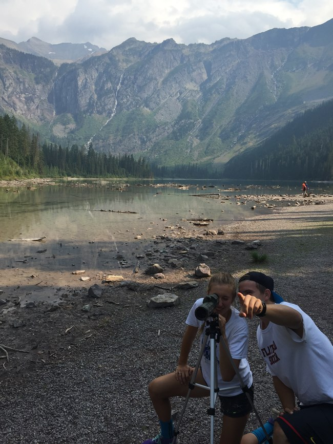 two people use a spotting scope in an alpine lake setting