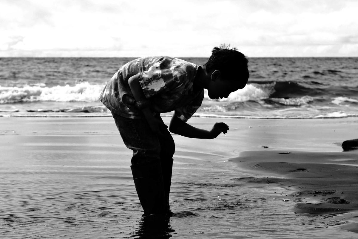 black and white silhouette of a child picking something out of the ocean
