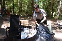 a ranger cleans a fire pit of trash