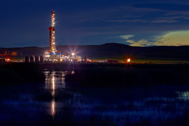 An oil rig drilling site emits bright lights into the atmosphere.
