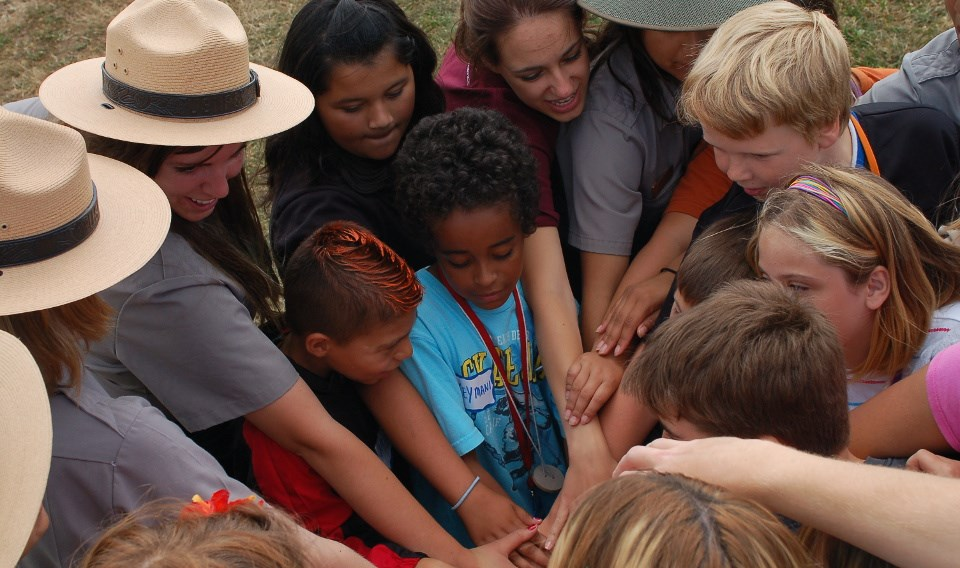 Group of park rangers and kids join hands