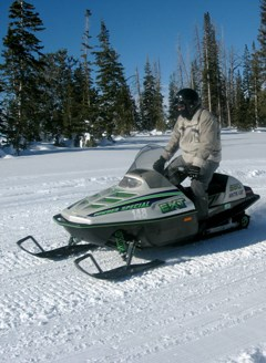 Person on a snowmobile in a winter landscape