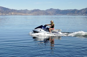 A woman on a personal watercraft on a lake with desert landscape in the background.