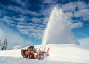 A snowplow blowing snow off of a road