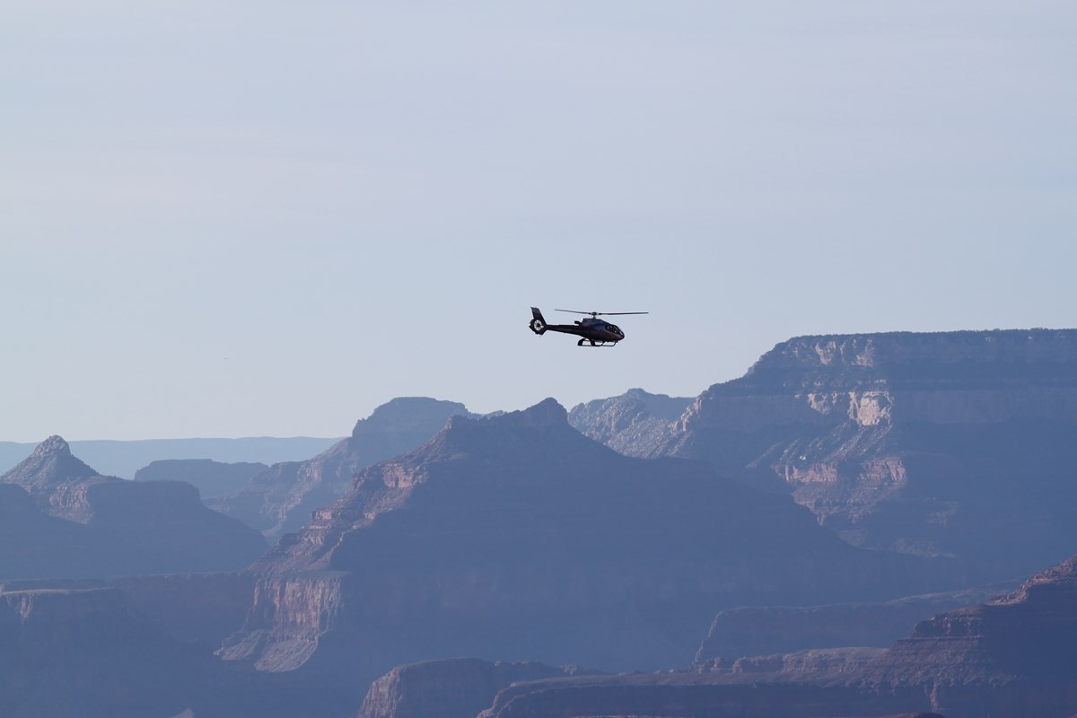 Dramatic buttes frame this view of a helicopter in flight at Grand Canyon National Park.