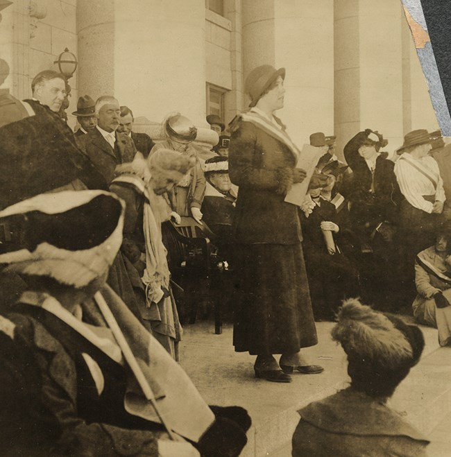 1915 photo of a woman wearing a suffrage sash speaking in front of a group of people