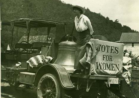 "black and white photo of woman standing on the flatbed of an early 20th century car next to a large bell and a sign ""Votes for Women'"