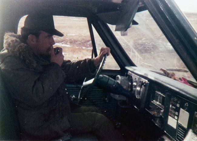 A uniformed man wears a heavy coat and talks on the radio inside a vehicle.