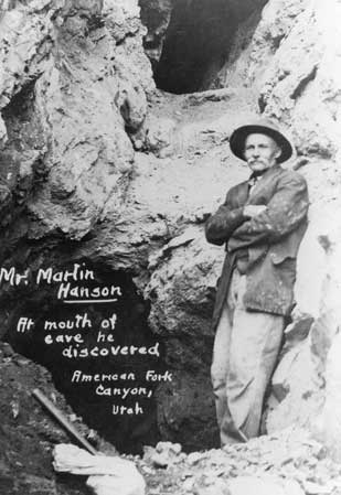 Martin Hansen stands at the mouth of the cave he discovered, Hansen Cave. The photo is in black and white, and Hansen is standing on a pile of rocks, just in front of the natural entrance.
