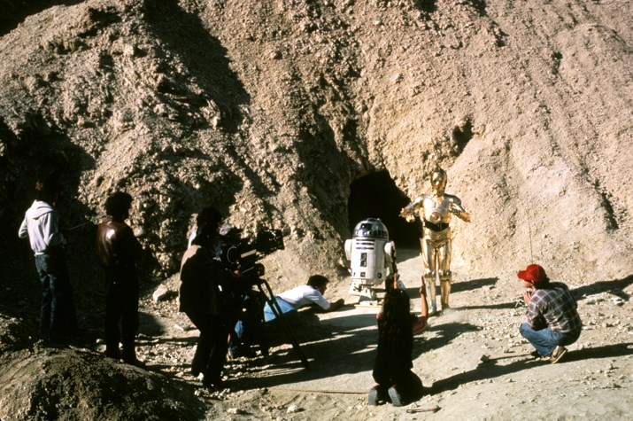 A group of adults stand and squat around a two robots, filming a scene in the desert.