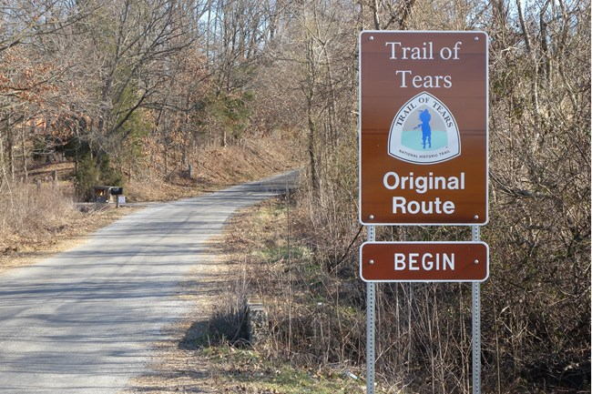 A brown sign indicating the Trail of Tears, next to a trail.