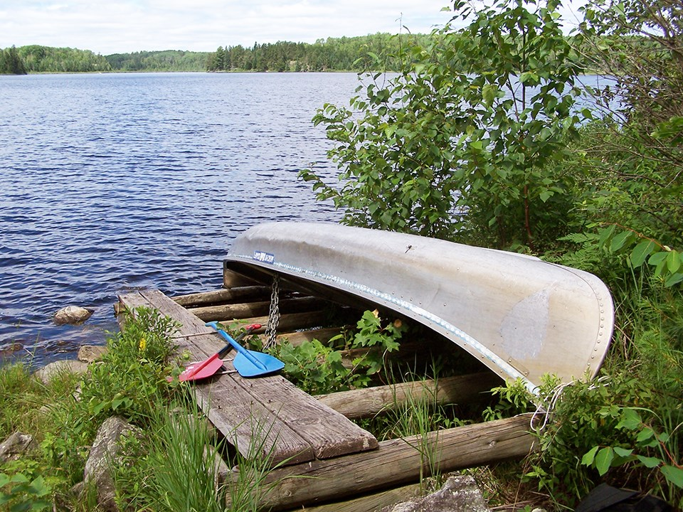 A canoe sits upside down on a wooden rack on the shores of a scenic lake, secured to the rack by a chain. Two paddles lay crossed next to the canoe.