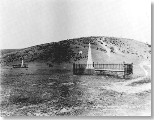 Historic photo of two wrought iron fenced enclosed grave areas, each with a tall white monument.