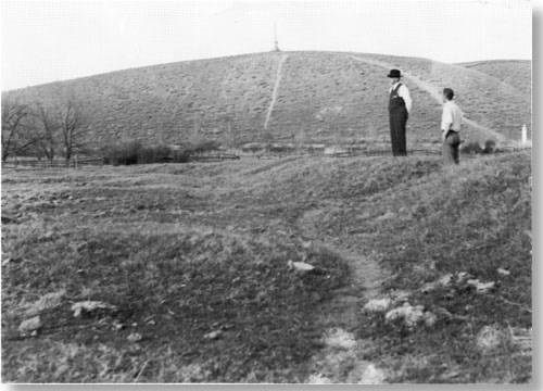 Historic photo of two men standing on small rise looking down. There is no water. Vegetation is very sparse.