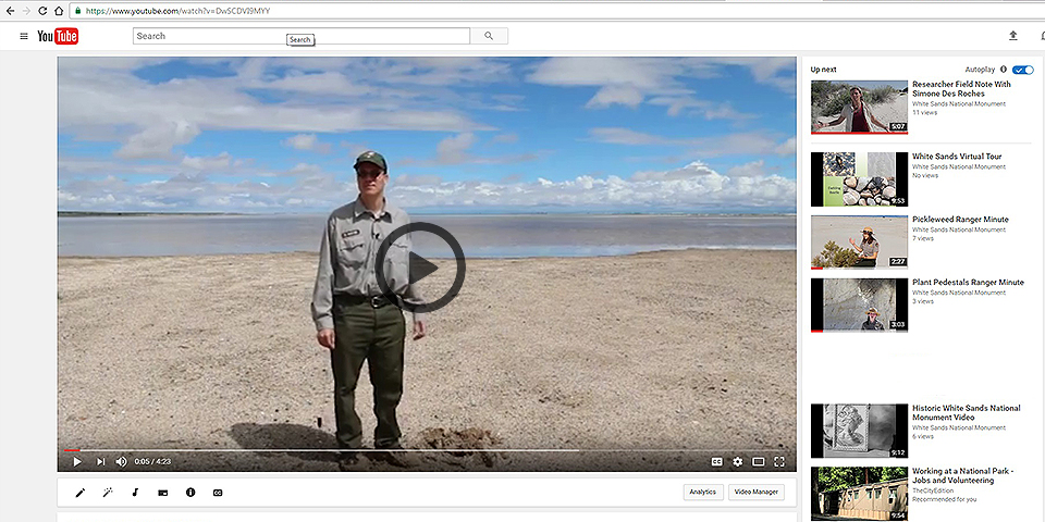 A video featuring a ranger standing in front of a lake under a cloudy sky
