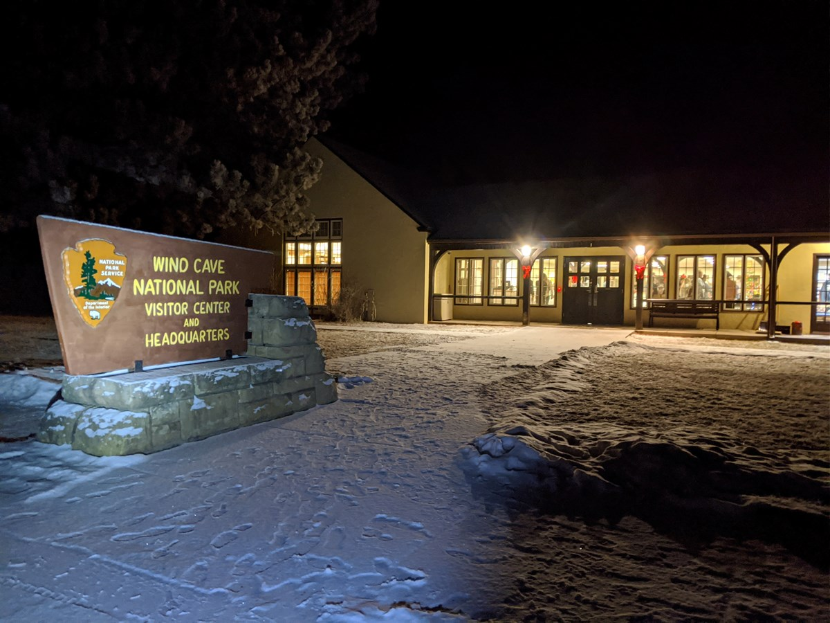Nighttime outside the visitor center with snow covering the ground.