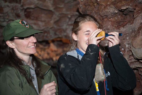 A park employee looks over the shoulder of a student reading a clinometer while in Wind Cave.