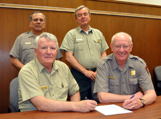 Two U.S. Forest Service rangers and two park superindentents signing agreement.