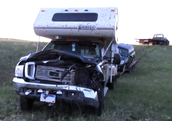 A pickup truck with a camper and towing a trailer has a smashed in front end from hitting bison.