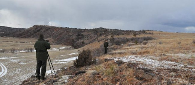Two rangers filming a video at a buffalo jump site on the Casey property