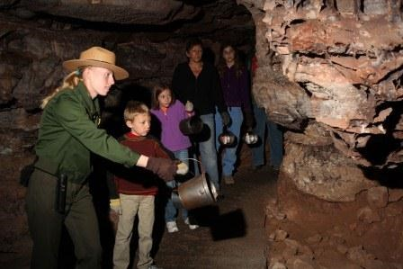A ranger-led tour with a family.  They are all holding candle buckets.
