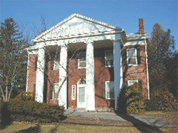 The Hunt House is a two story red brick residence with four decorative white columns and portico on the front.