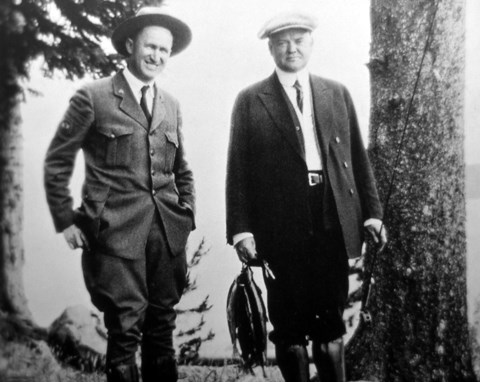 A man in an early park ranger uniform next to a man holding fish and a fishing rod