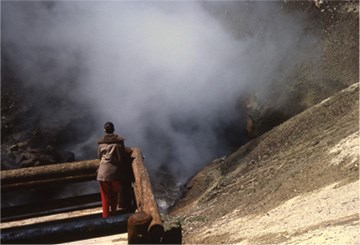 A person stands in front of rising steam from a large vent in a hillside above blue water