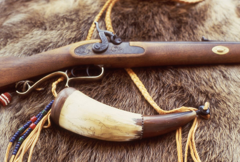 European American rifle and powder horn resting on fur.