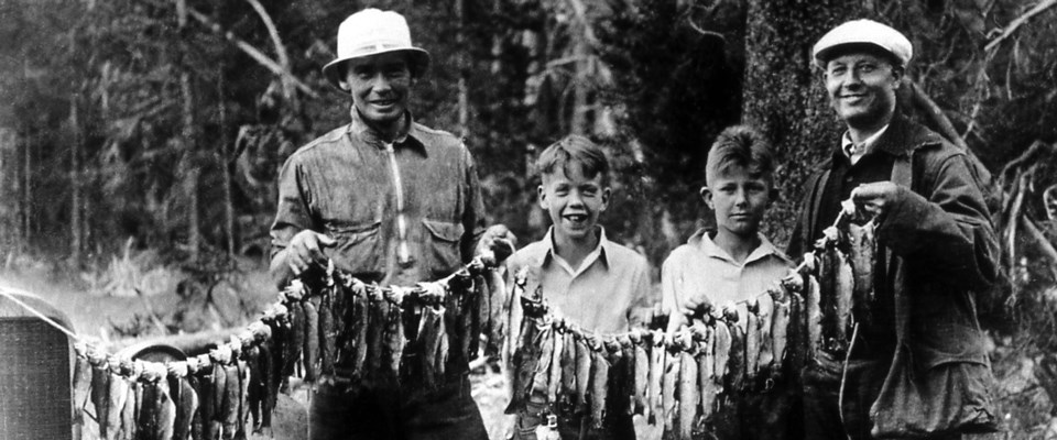 Two men and two boys hold a line of fish in a historic photo