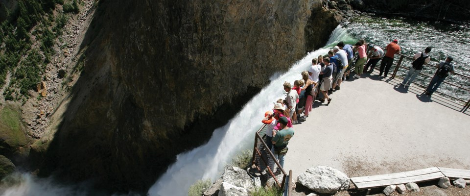 Looking down from a hill to people lining the edge of a fence overlooking a waterfall