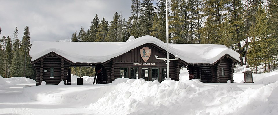A log building with covered car lanes covered in snow