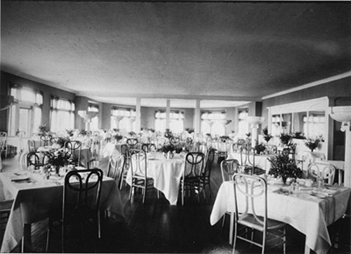 Historic black and white photo of the Lake Hotel Dining Room with tables and chairs. Circa 1930.