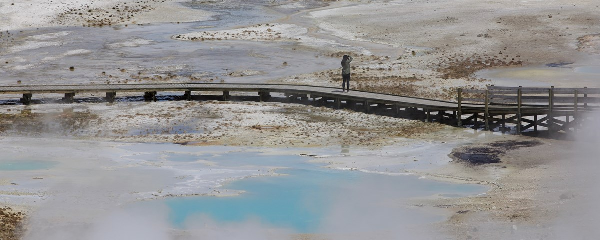 A lone visitor stands on a boardwalk and photographs the nearby hot springs.