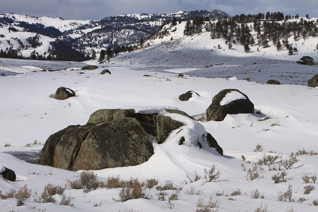 Large boulders dot the valley, both covered in snow.