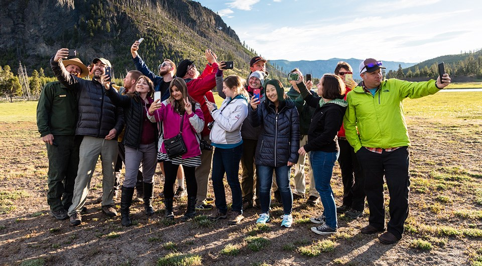 A group of people show their enthusiasm for Yellowstone by taking a group photo.