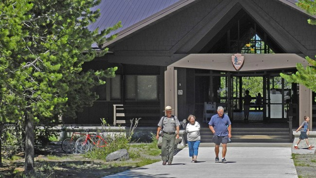 A ranger walks with a couple of visitors along a concrete path in front of the visitor center.
