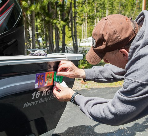 Applying a Yellowstone AIS sticker to a boat