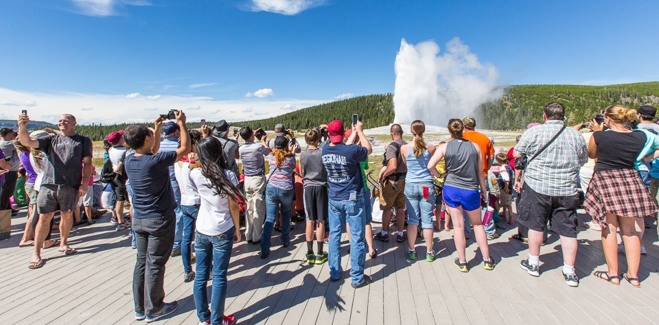 People using cell phones during an eruption of Old Faithful