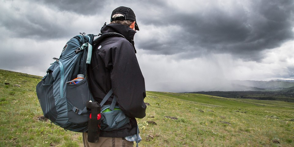 A hiker watches an oncoming storm on Specimen Ridge