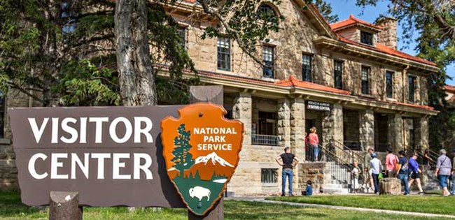 "Large brown sign reads ""Visitor Center"" with NPS arrowhead on it standing before the stone building that is home to the Albright Visitor Center."