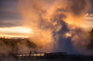 The sun sets in the steam from a geyser drifting above a person standing on a boardwalk.